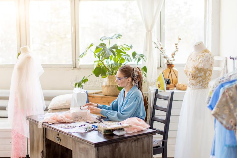 Smiling young dressmaker woman sews clothes on a sewing machine in her workshop royalty free stock photo