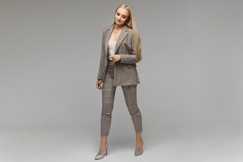 Smiling young elegant businesswoman with bright makeup and in suit looking down in the studio,  on grey royalty free stock photo