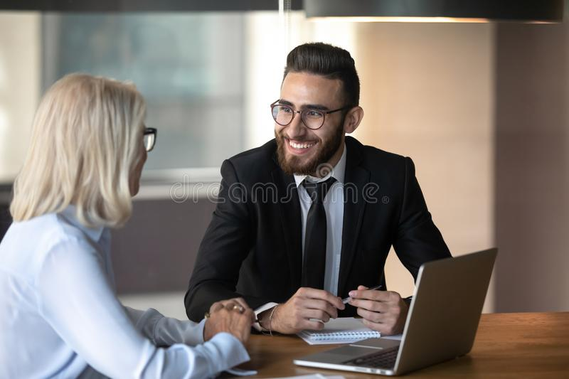 Smiling young employee and mature businesswoman working together stock image