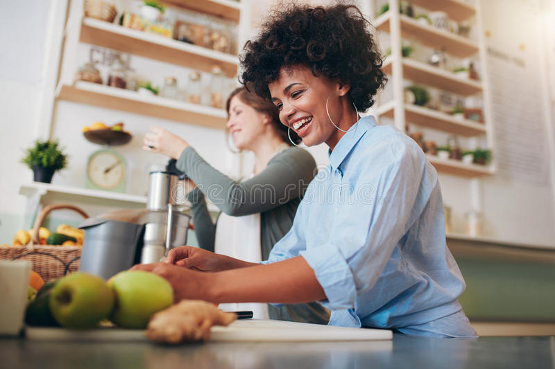Smiling young employees working at juice bar stock photography