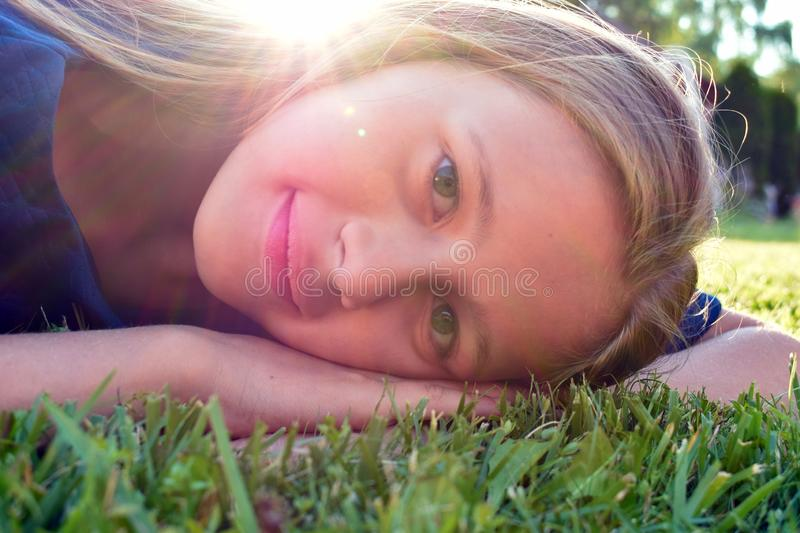 Smiling young face of girl. Nice child rejoices royalty free stock photography