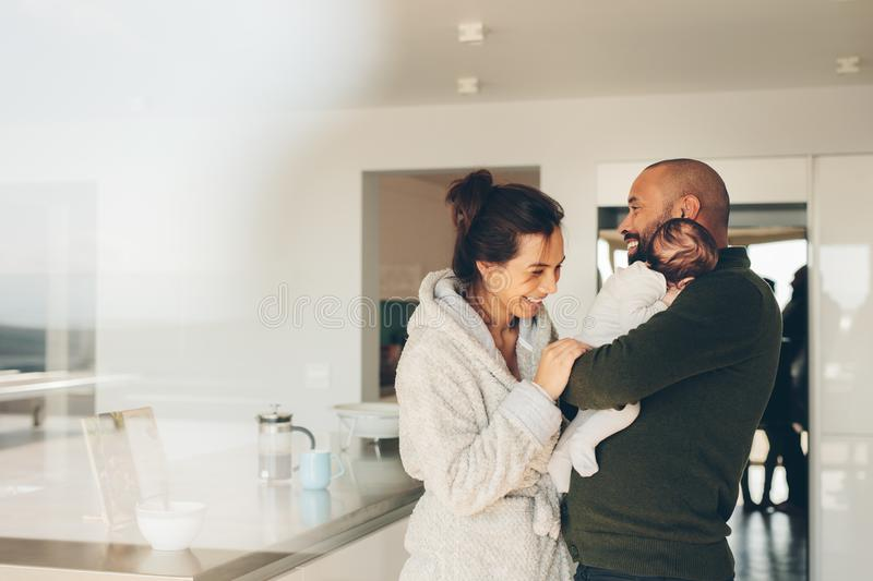 Smiling young family in kitchen royalty free stock photo