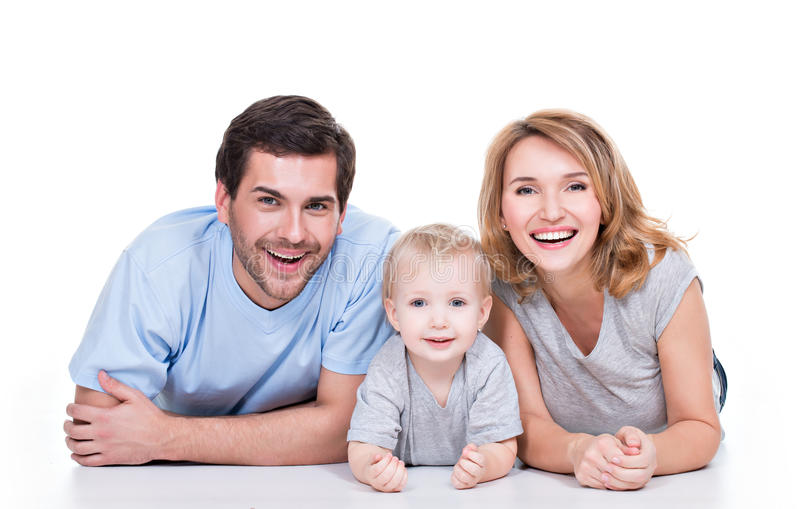 Smiling young family with little child. Photo of the smiling young parents with little child lying on the floor - isolated on white background stock photography