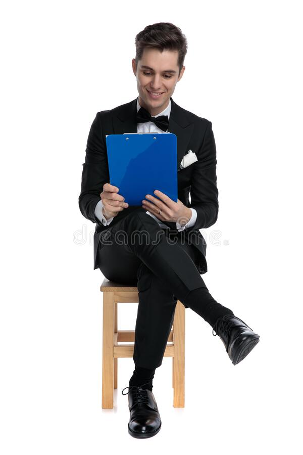 Smiling young fashion guy holding and reading from clipboard stock photography