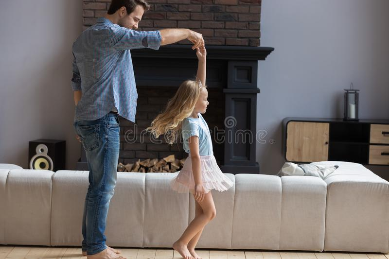 Smiling young father twisting happy little preschool blonde daughter. royalty free stock photo
