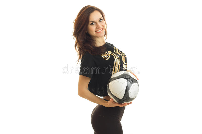 Smiling young female athlete stands in the Studio with a football in his hands royalty free stock image