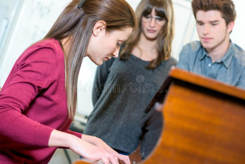 Smiling young female customer choosing synthesizer in store stock images