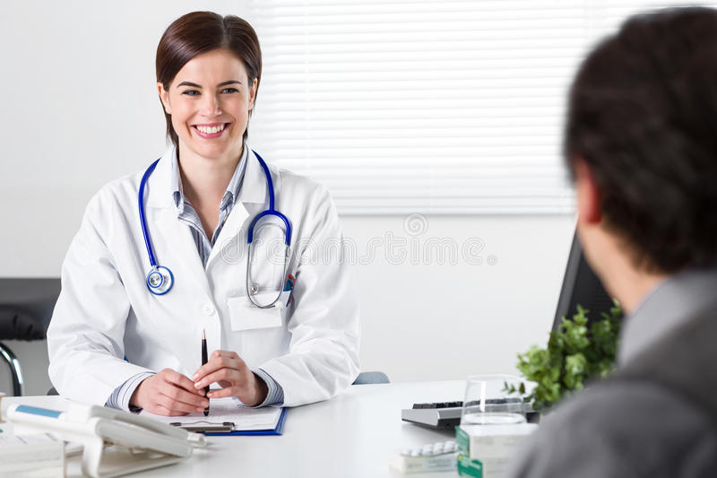 Smiling Young female doctor listening to patient royalty free stock images