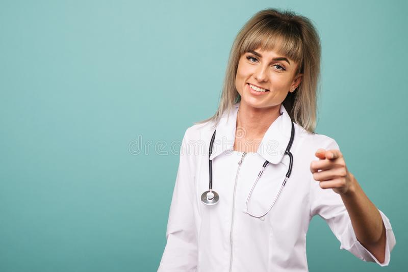 Smiling young female doctor with a stethoscope points into the camera with her fingers stock photography