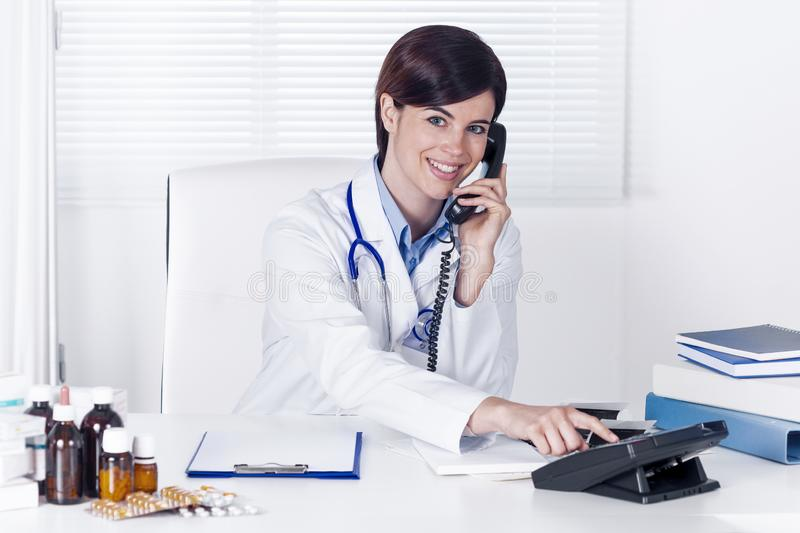 Smiling young female doctor talking on a telephone stock image