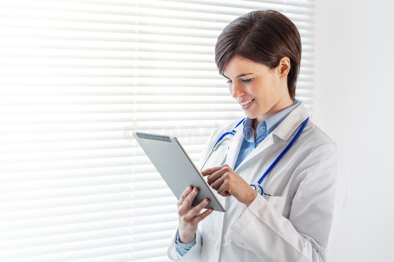 Smiling confident young female doctor using a tablet computer. Smiling young female doctor using a tablet computer standing staring out of a high key window with stock image