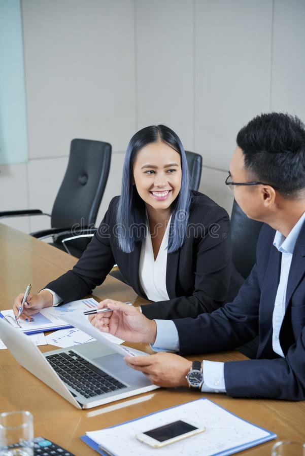 Talking positive collegues. Smiling young female entrepreneur talking to coworker at meeting royalty free stock photography