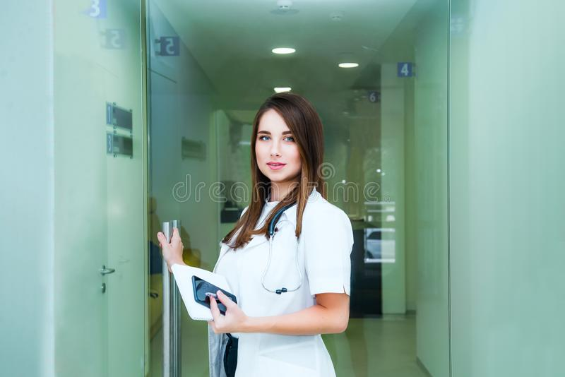 Smiling young female medical professional, doctor with stethoscope and smart phone looking at camera and opening the door to her. Practice or hospital royalty free stock image