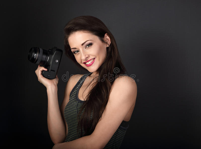 Smiling young female professional photograph holding photo camera and looking happy on dark grey background with empty copy space stock photography