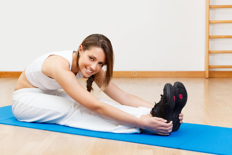 Smiling young female stretching on the floor sitting on mat royalty free stock images