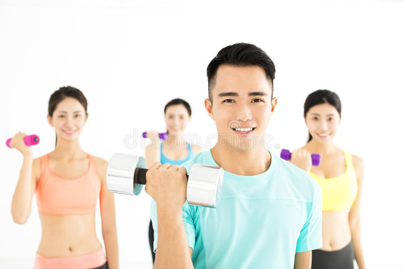 Smiling young fit group stretching in gym stock photography