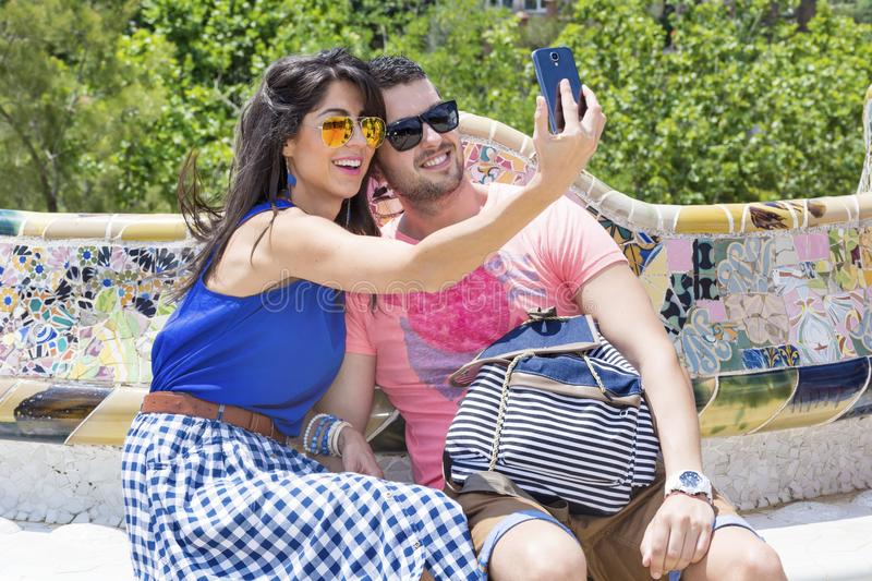 Beautiful love couple making selfie with phone. Smiling young friends in Park Guel public park ,Barcelona,Spain.Summer vacation stock photography