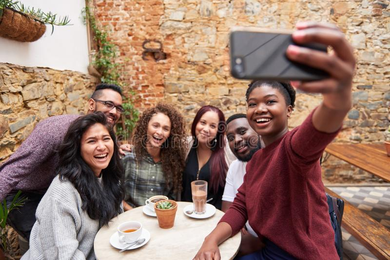 Smiling young friends taking selfies together in a cafe courtyard. Diverse group of smiling young friends taking a selfie together while sitting around a table stock image