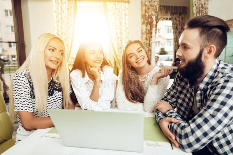 Smiling young friends using laptop in coffee shop royalty free stock image