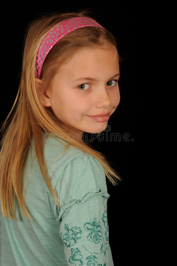 Smiling young girl. Half body portrait of smiling young girl looking back over shoulder, black background royalty free stock photos