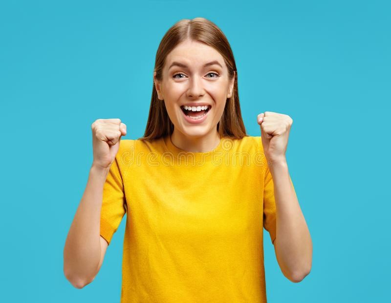 Smiling young girl clenched fistsas as symbol of success victory and exclaimed loudly. royalty free stock photos
