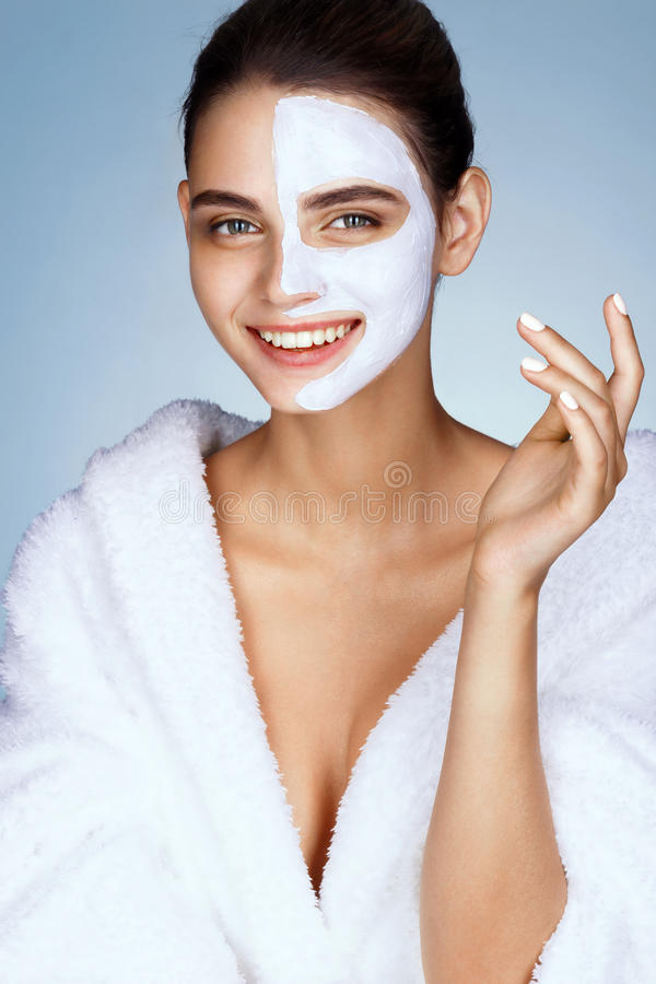 Smiling young girl with cosmetic mask on her face. stock image