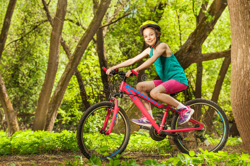 Smiling young girl cycling through spring woodland. Side view picture of smiling young girl in bicycle helmet, cycling through spring park stock image