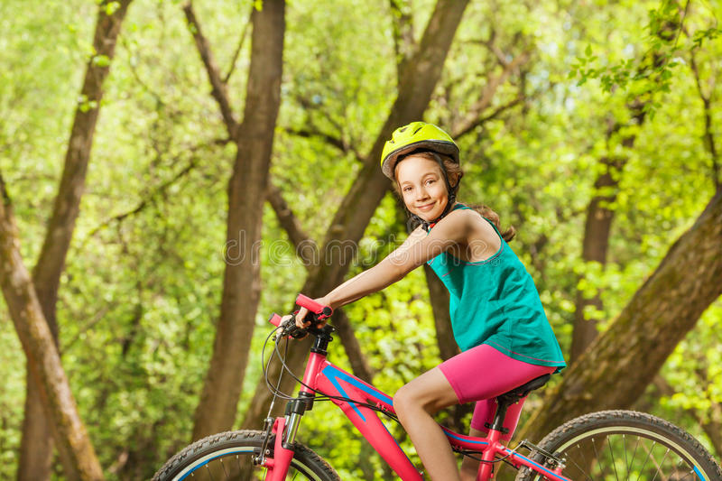 Smiling young girl cycling through sunny woodland. Side view portrait of smiling young girl in bicycle helmet, cycling through sunny woodland stock image