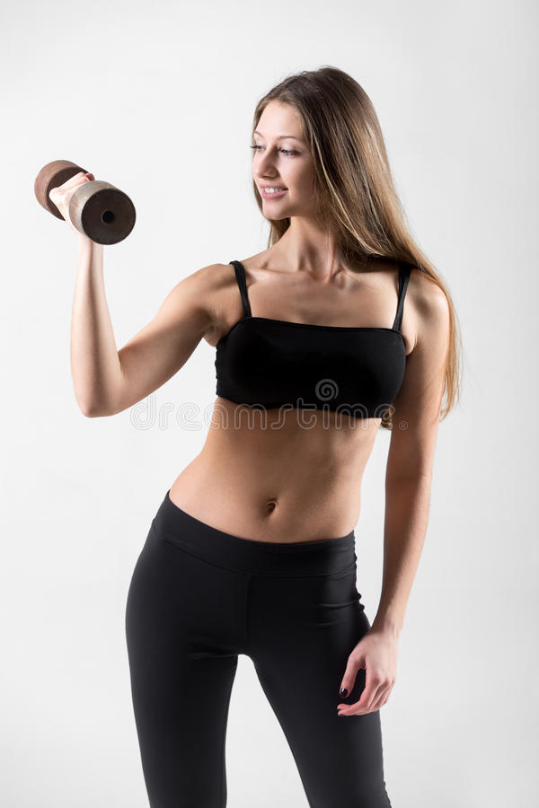 Smiling young girl doing weightlifting royalty free stock photos