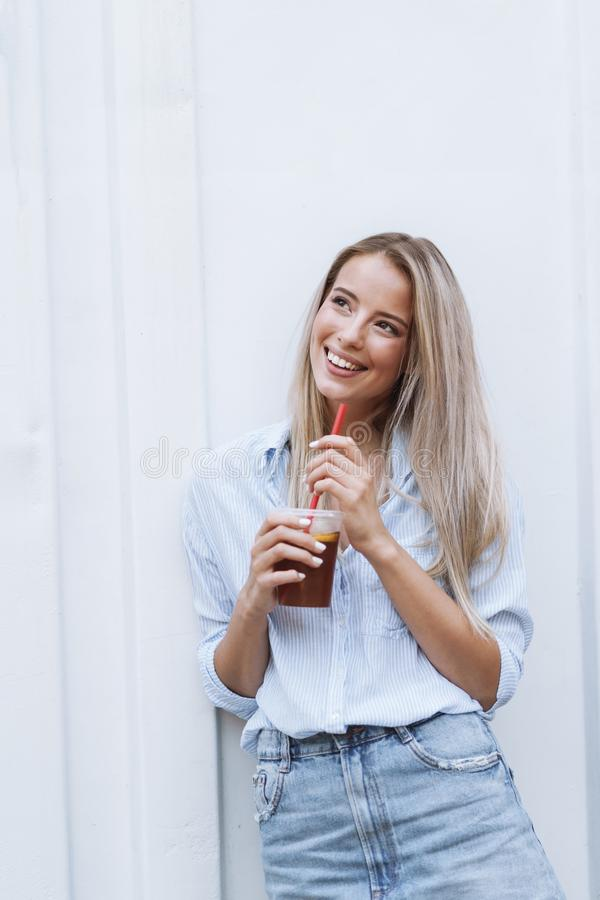 Smiling young girl drinking juice while standing royalty free stock photos
