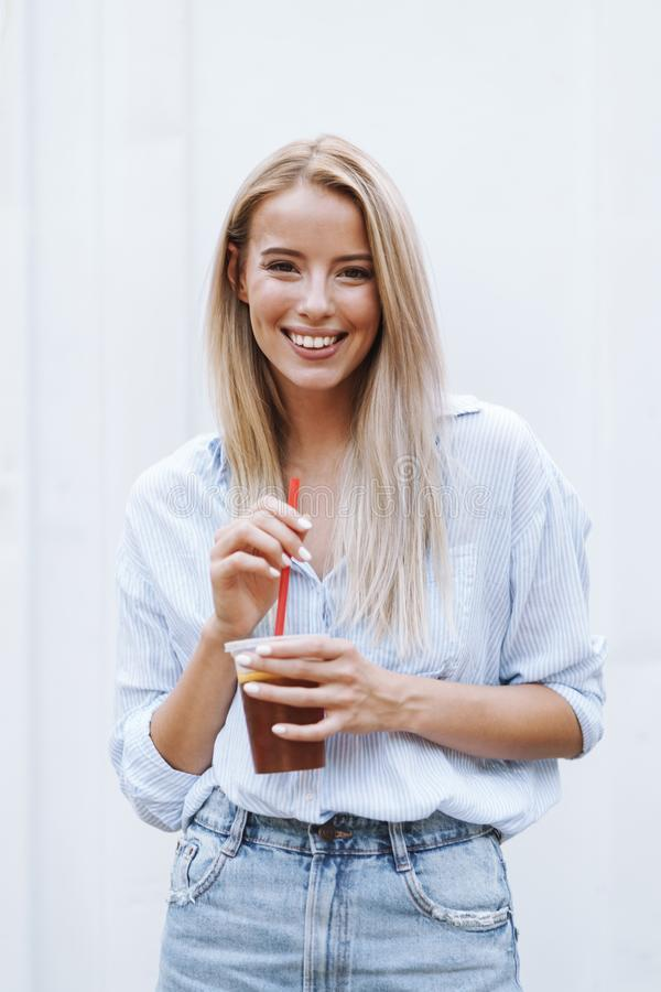 Smiling young girl drinking juice while standing stock image