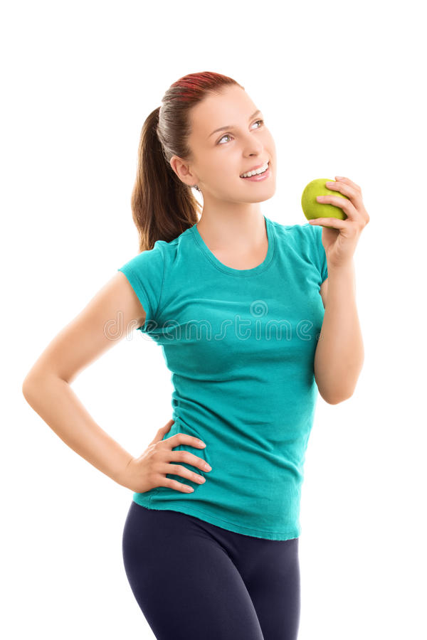 Smiling young girl in fitness clothes holding an apple. A portrait of a smiling beautiful young girl in fitness clothes holding an apple, isolated on white royalty free stock images