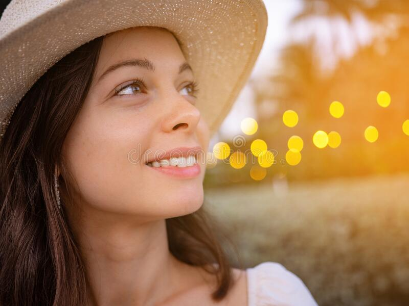 Smiling young girl in a hat outdoors stock images