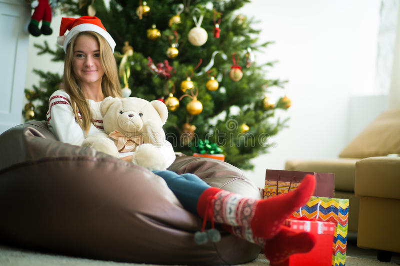 Smiling young girl hugs teddy bear in christmas eve. Beautiful smiling girl in christmas cap and socks sitting and hugging with white teddy bear. Decorated stock photos