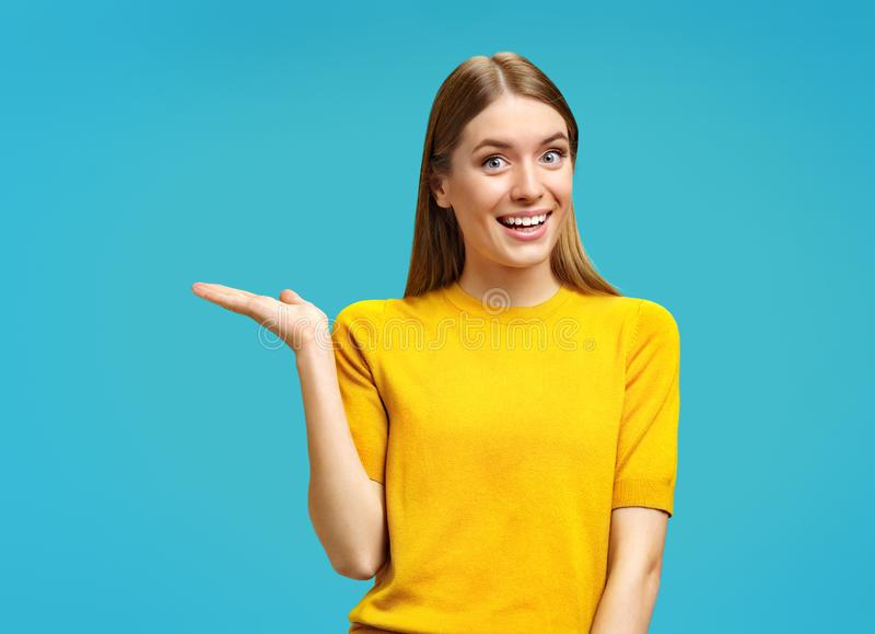 Smiling young girl points aside her open palm, shows copy space for your advert. royalty free stock photo