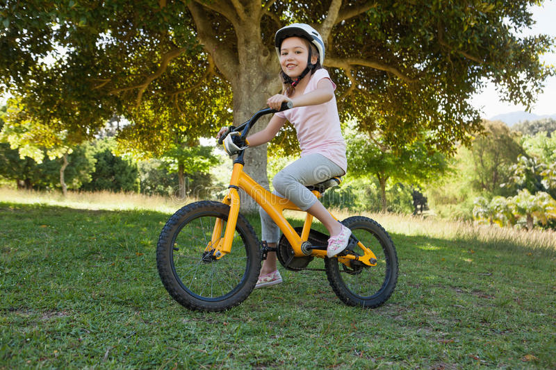 Smiling young girl riding bicycle at park royalty free stock image