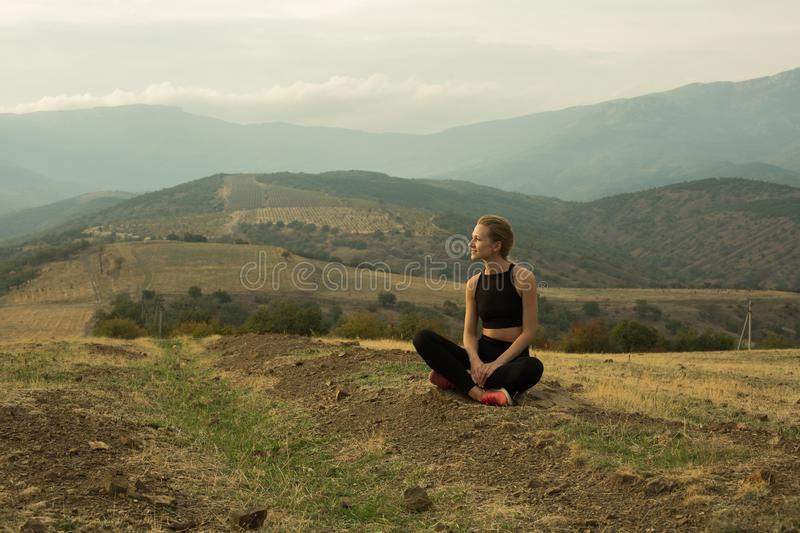 Happy woman enjoying landscape in mountains. Smiling young girl is squatting crosslegged among dried yellow grass, meadow, in mountains, cloudy sky royalty free stock image