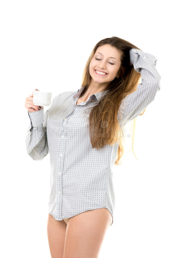 Smiling young girl stretching with pleasure enjoying morning coffee royalty free stock photography