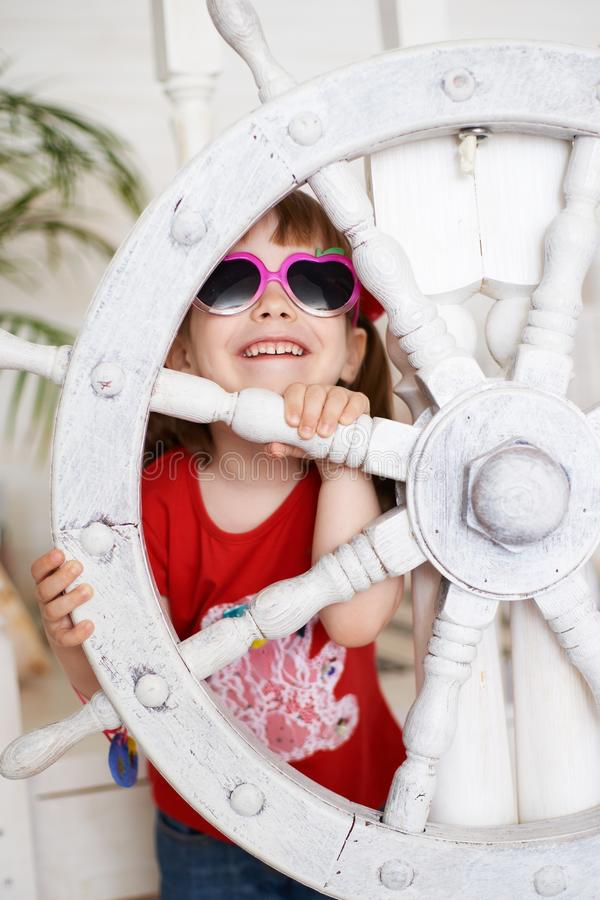 Smiling young girl in sunglasses with steering wheel stock photo