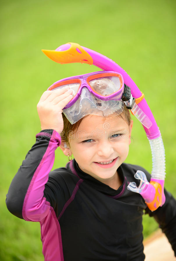 Smiling young girl with swimming goggles and snorkel. After getting out of the pool royalty free stock photo
