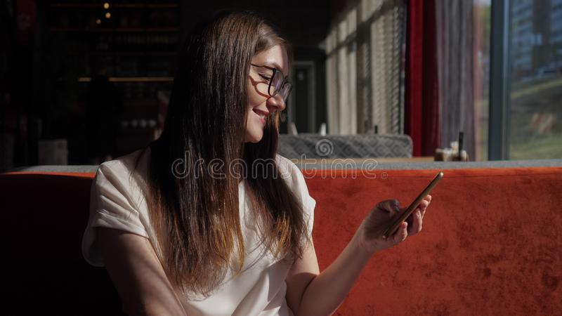 Smiling young girl texting on mobile phone in cafe royalty free stock images