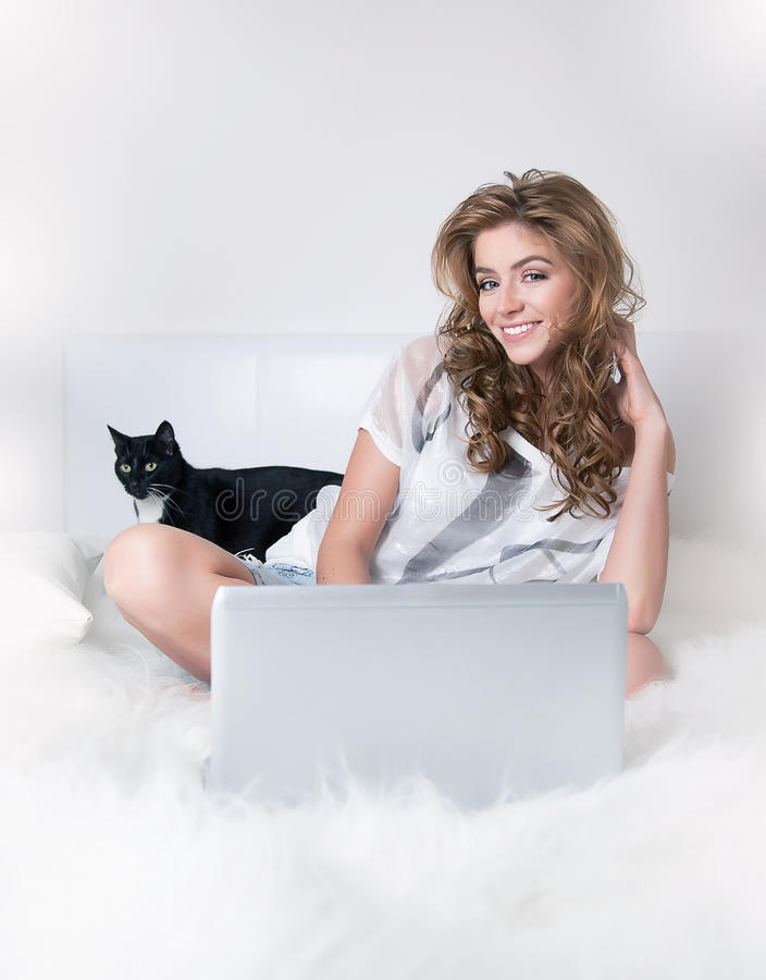Smiling young girl in white bed with black cat