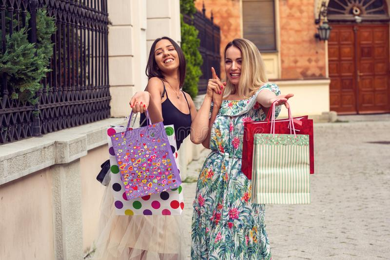 Smiling girlfriends with shopping bags stock photos