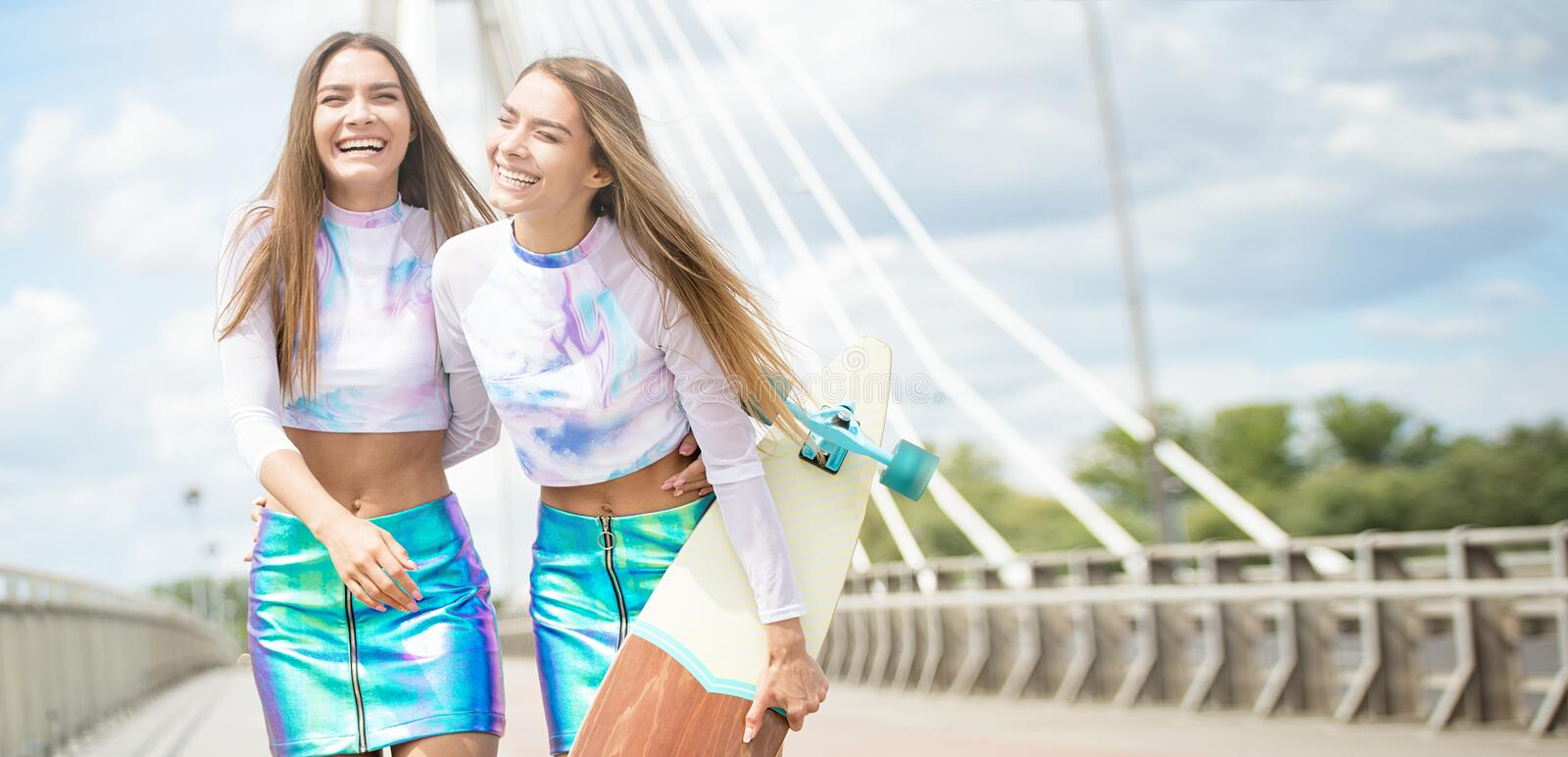 Smiling young girls with skateboard posing outdoor. stock photos