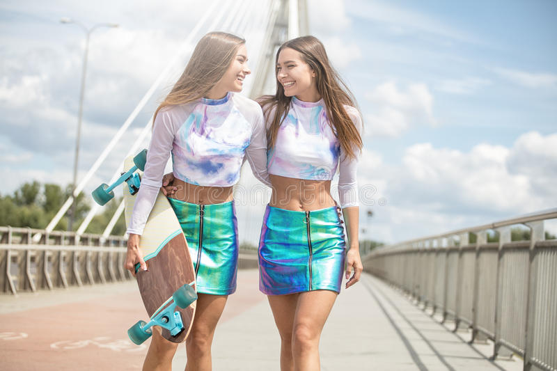 Smiling young girls with skateboard posing outdoor. royalty free stock images