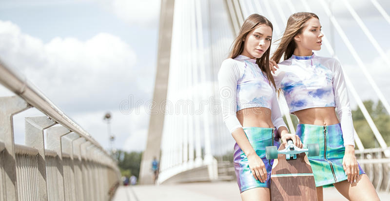 Smiling young girls with skateboard posing outdoor. royalty free stock photography
