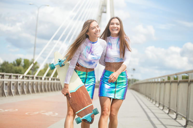 Smiling young girls with skateboard posing outdoor. stock photo