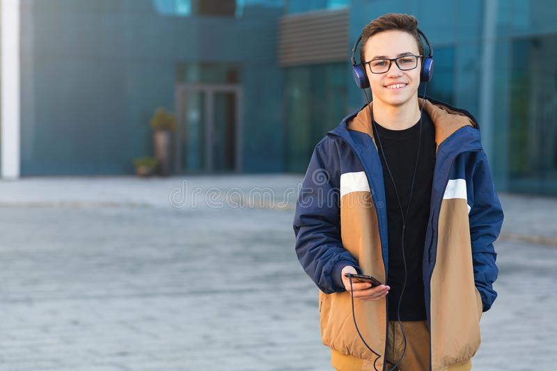 Smiling young guy listening to music, holding the phone outdoors. Copy space stock photos