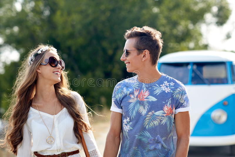 Smiling young hippie couple over minivan car royalty free stock photo