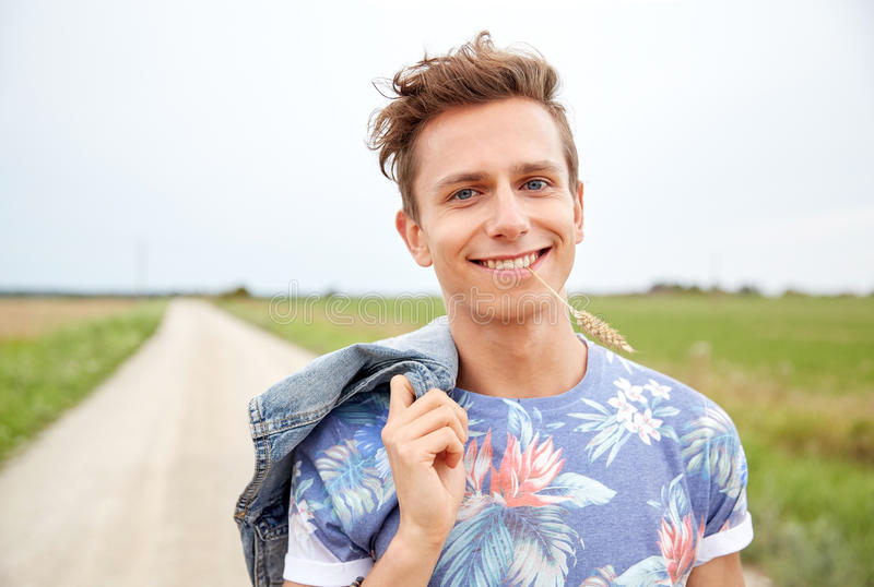 Smiling young hippie man on country road. Nature, summer, youth culture and people concept - smiling young hippie man on country road chewing rye spike stock image